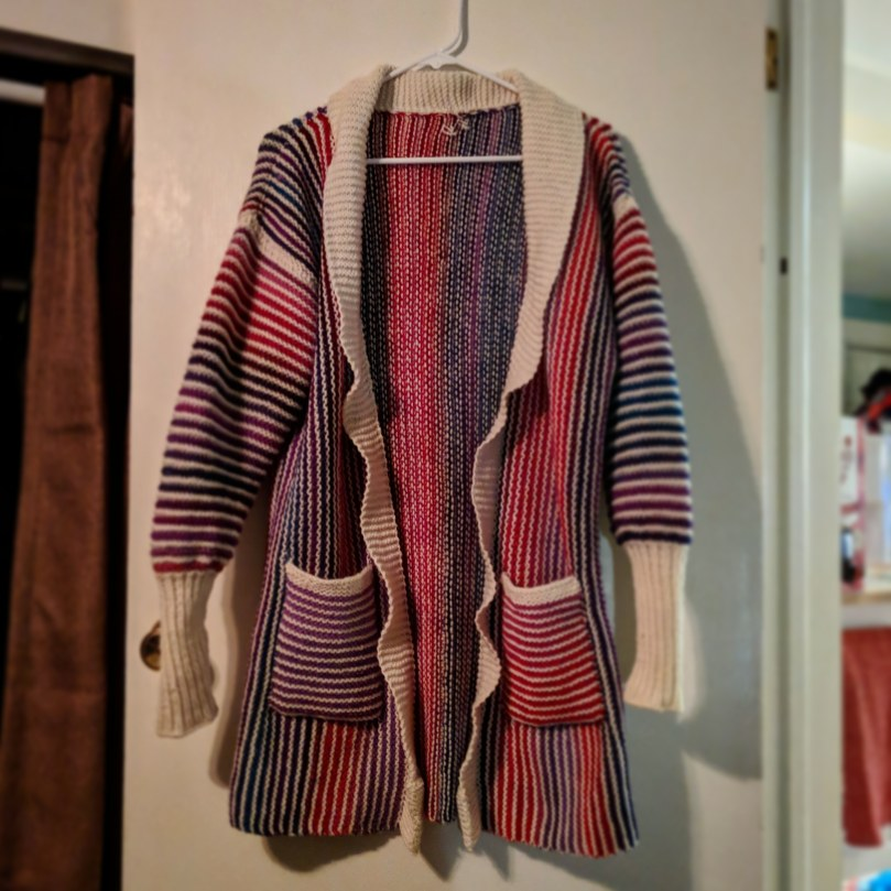 Completed cardigan hanging on a hanger
