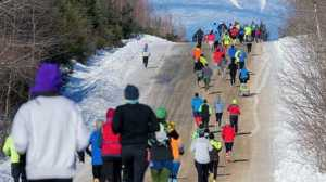 A large group of runners running uphill as part of the either the marathon or half marathon at Millinocket.