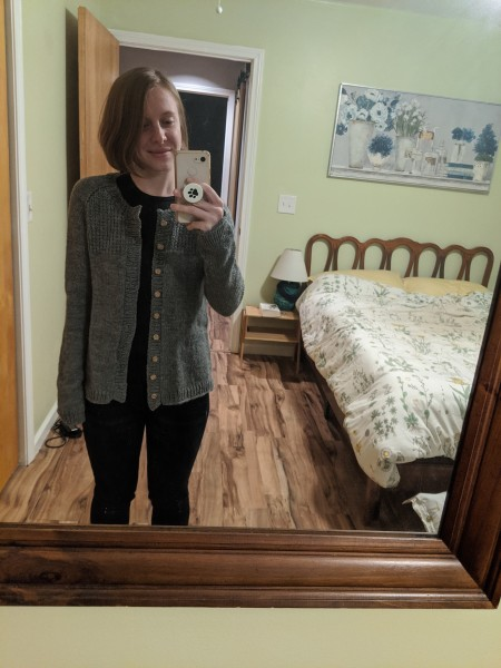 A young woman takes a selfie of herself in her bedroom mirror wearing a hand knit grey cardigan.