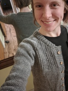 A young woman taking a photo of herself with her back to a mirror in hopes of showing off the texturing of both the front and back pieces of the cardigan she is wearing.