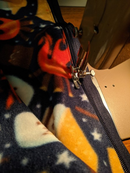 A zipper being attached to fabric using a sewing machine
