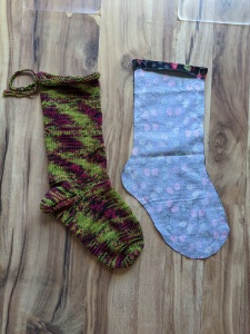 Fabric sewn in the shape of a stocking next to a handknit stocking.
