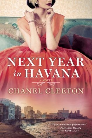 A young woman wearing a sheer sleeved princess cut reddish pink dress, a pearl necklace and a heather in her hair on a turquoise couch. Her dress fades into the Havana city line.
