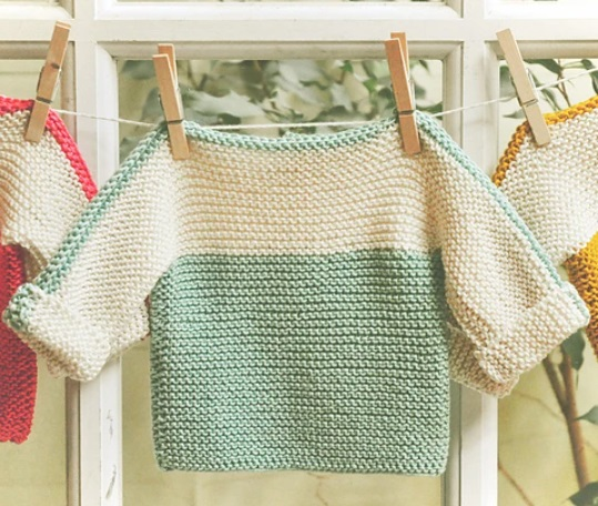 A garter stitch sweater hanging on a clothes line. The body of the sweater is blue, the sleeves and chest are white and there is a blue strip along the top of the sleeves and neckline.