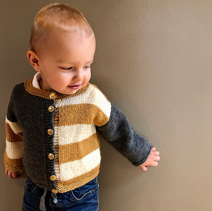 A toddler wearing a handknit buttoned cardigan. Half of the sweater is a solid grey and the other half is white and gold stripped. The sleeves on either side of the cardigan are the opposite (the grey side has white and gold striped sleeves, the stripped side has a solid grey sleeve).