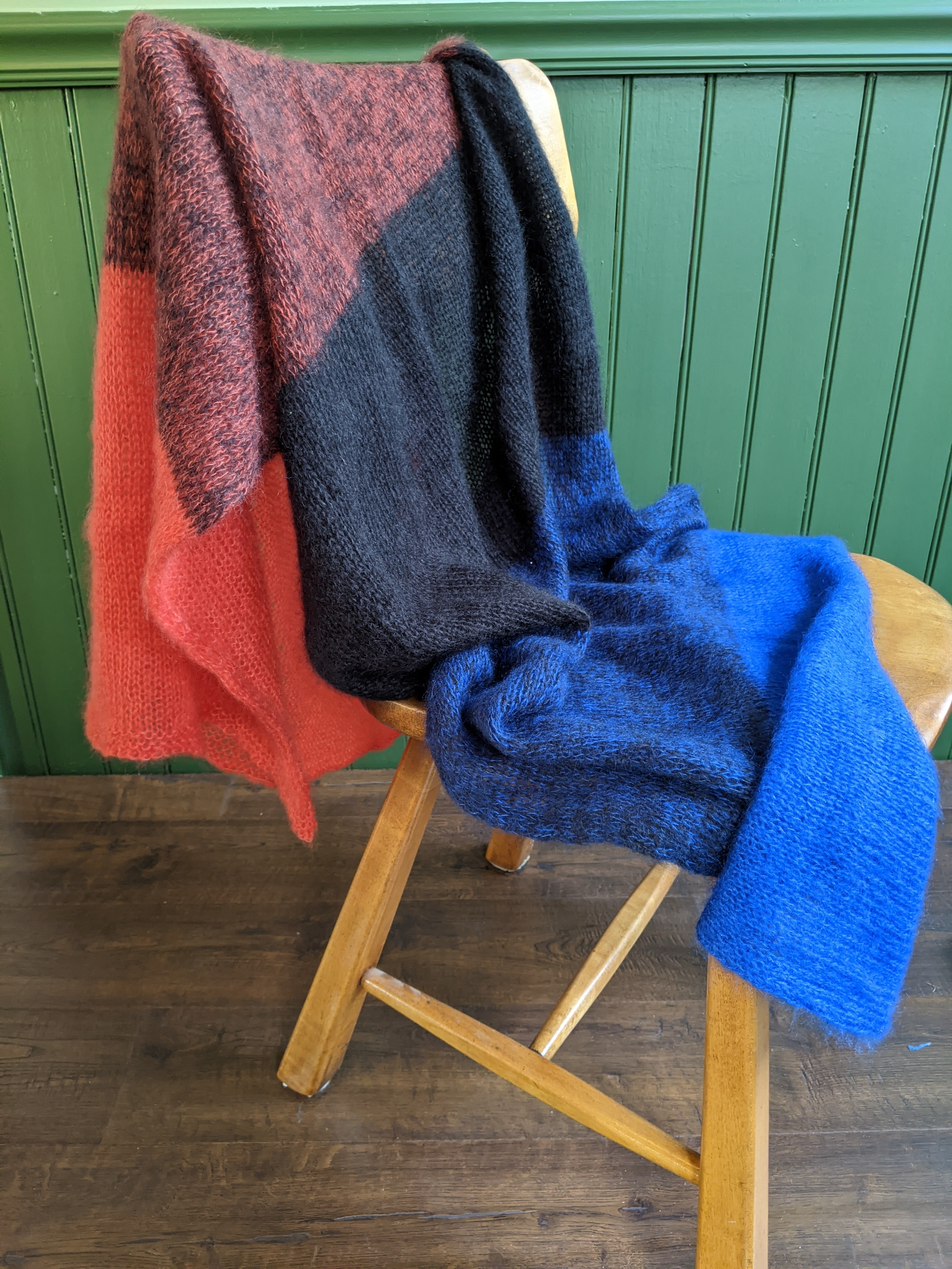 A completed Cold Spring shawl, knit in mohair yarn. The stripes are orange, orange black, black, blue black and blue.
