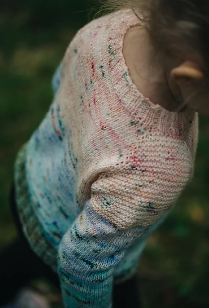 A little girl facing away from the camera wearing a sweater that fades from pink to blue to green.