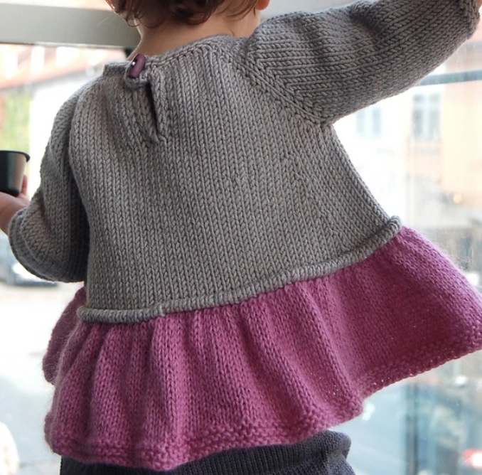 A gray handknit sweater with a pink ruffled bottom.