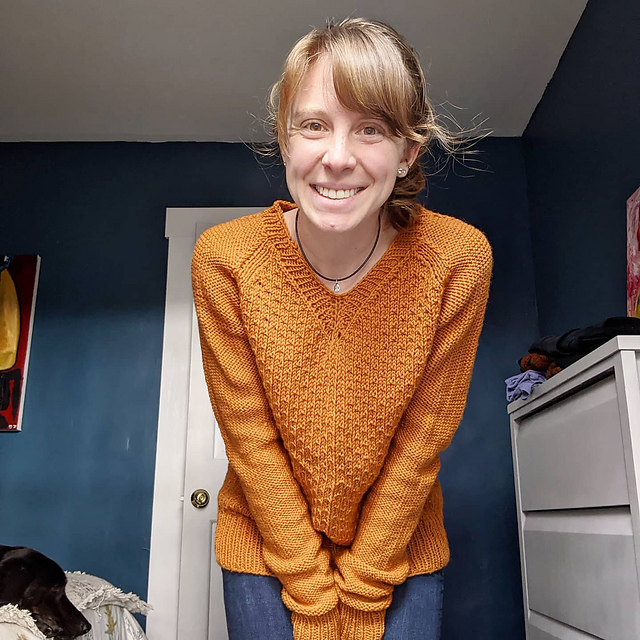 A young woman wearing a textured yellow orange handknit sweater.