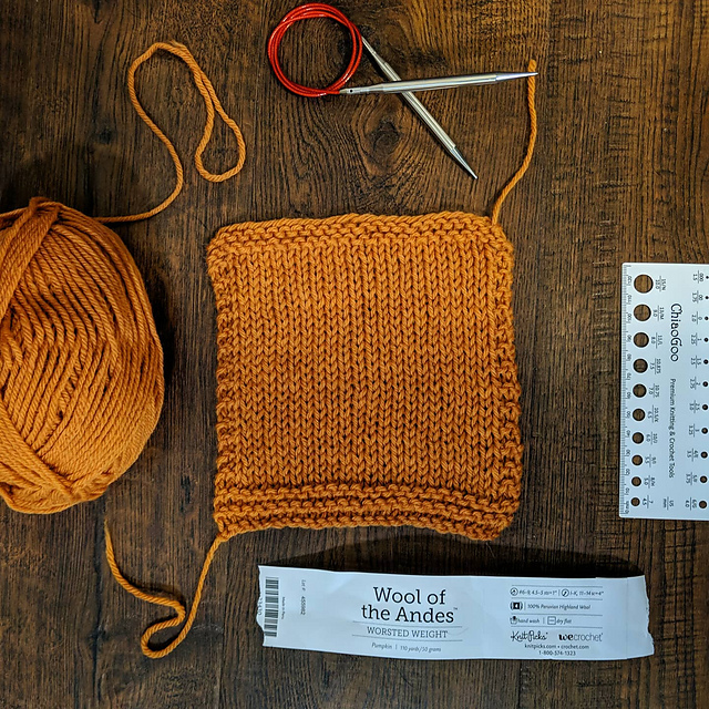 Yellow orange yarn knit into a stockinet stitch gauge swatch.
