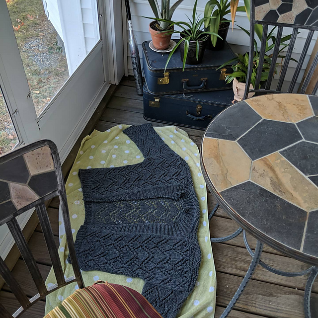 Finished Garnered Cardigan laying on a towel in an enclosed porch.