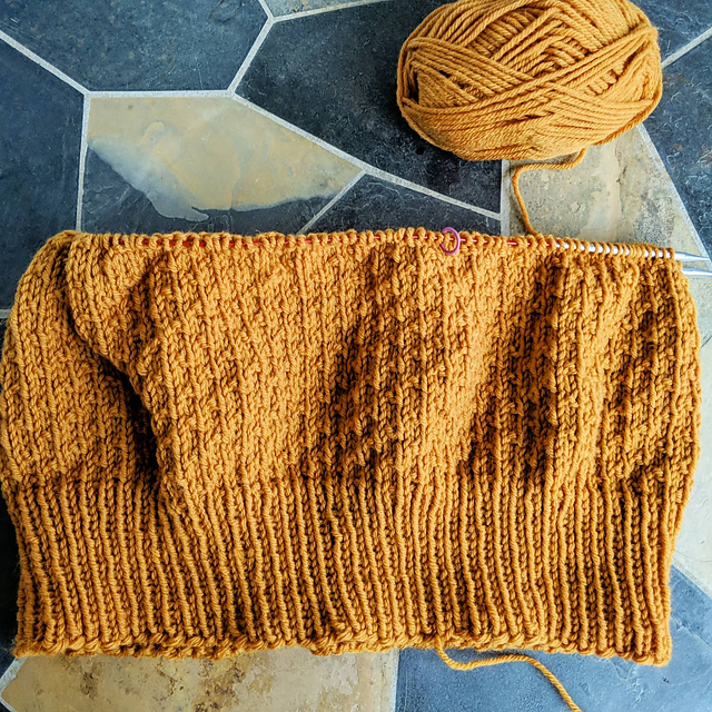 About 8 inches of an in progress yellow orange handknit sweater, 3 inches of bottom ribbing and 5 inches of broken seed stitch.