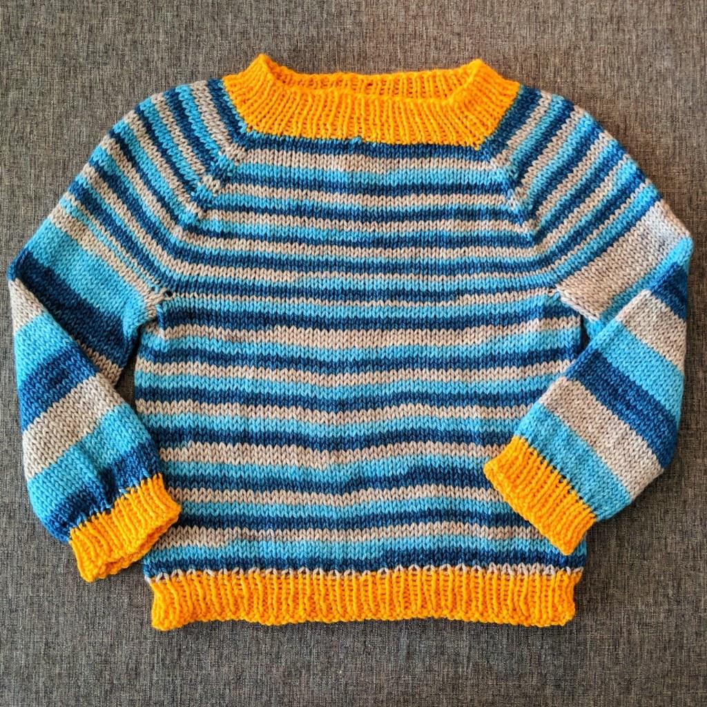 A light blue, dark blue and grey stripped baby sweater with orange cuffs.