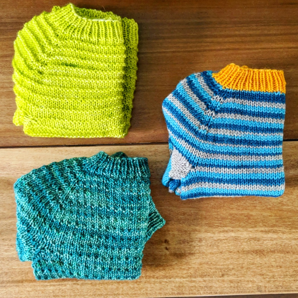 Three folded baby sweaters, the top left is a lime green knit baby sweater with purl rows every fourth row to create a textured stripe. The bottom left is a teal baby sweater with a waffle texture throughout. The final sweater is folded to the right and in the middle of the previous to, it is a light blue, dark blue and grey stripped baby sweater with orange cuffs.