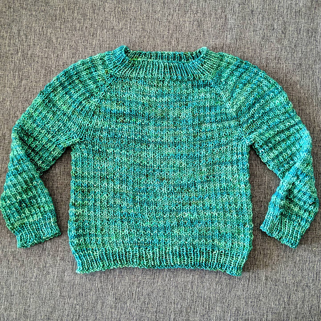 A teal baby sweater with a waffle texture throughout.