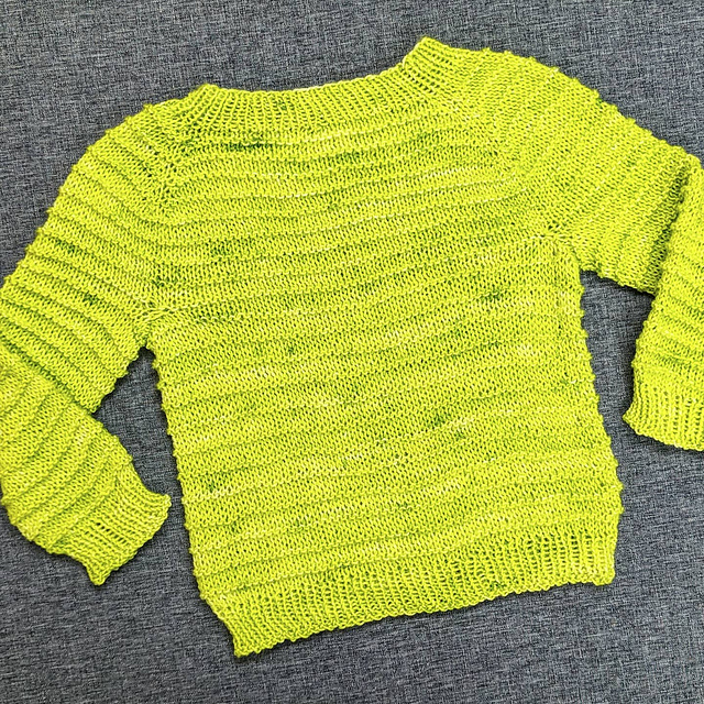 A lime green knit baby sweater with purl rows every fourth row to create a textured stripe.