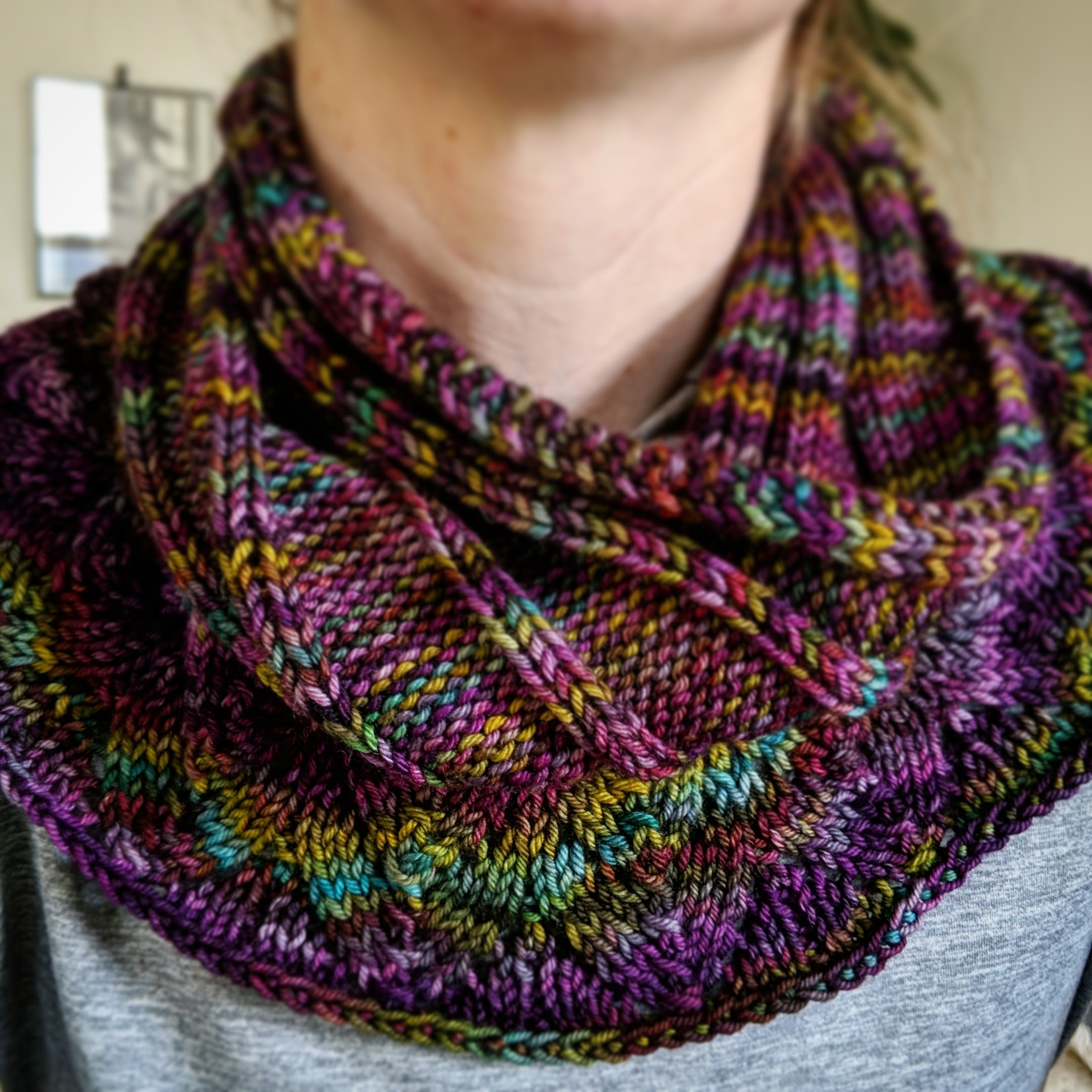 Close up of a multi colored ribbed cowl with lace edging being worn on a woman's neck.