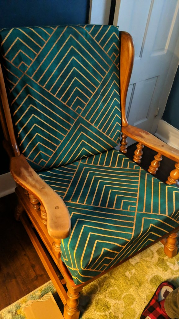 Patinaed wooden chair with gold patterned turquoise cushions.