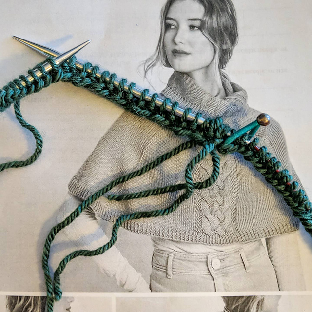 Freshly joined ribbing on circular knitting needles. The green project has a black and white photo of a woman wearing a capelet with a cable down the front center.