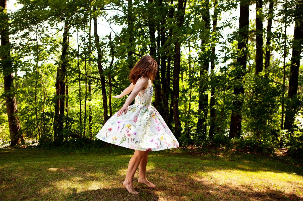 A young woman twirling with her arms stretched wide wearing a white dress with a floral print.