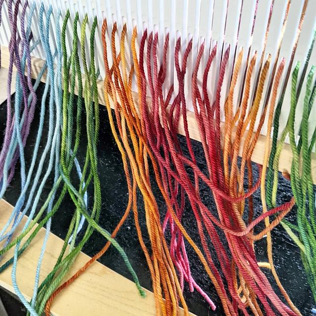 Cut and treaded strands of yarn on a loom.