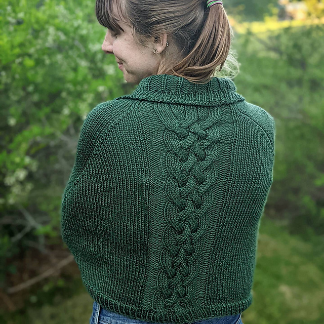 Close up of a woman's torso from behind. She's wearing a green capelet with a cable down the back center.
