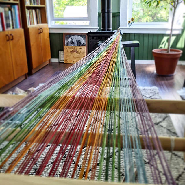 Yarn traveling from a cricket loom to a warping peg in the distance. The yarn is arranged in a rainbow of colors.
