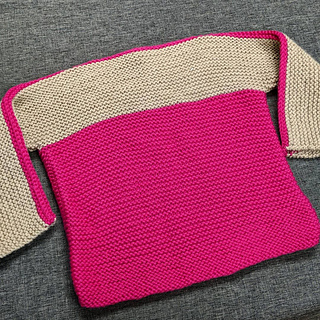 Baby sweater with a pink body and a beige strip creating the arms and chest.