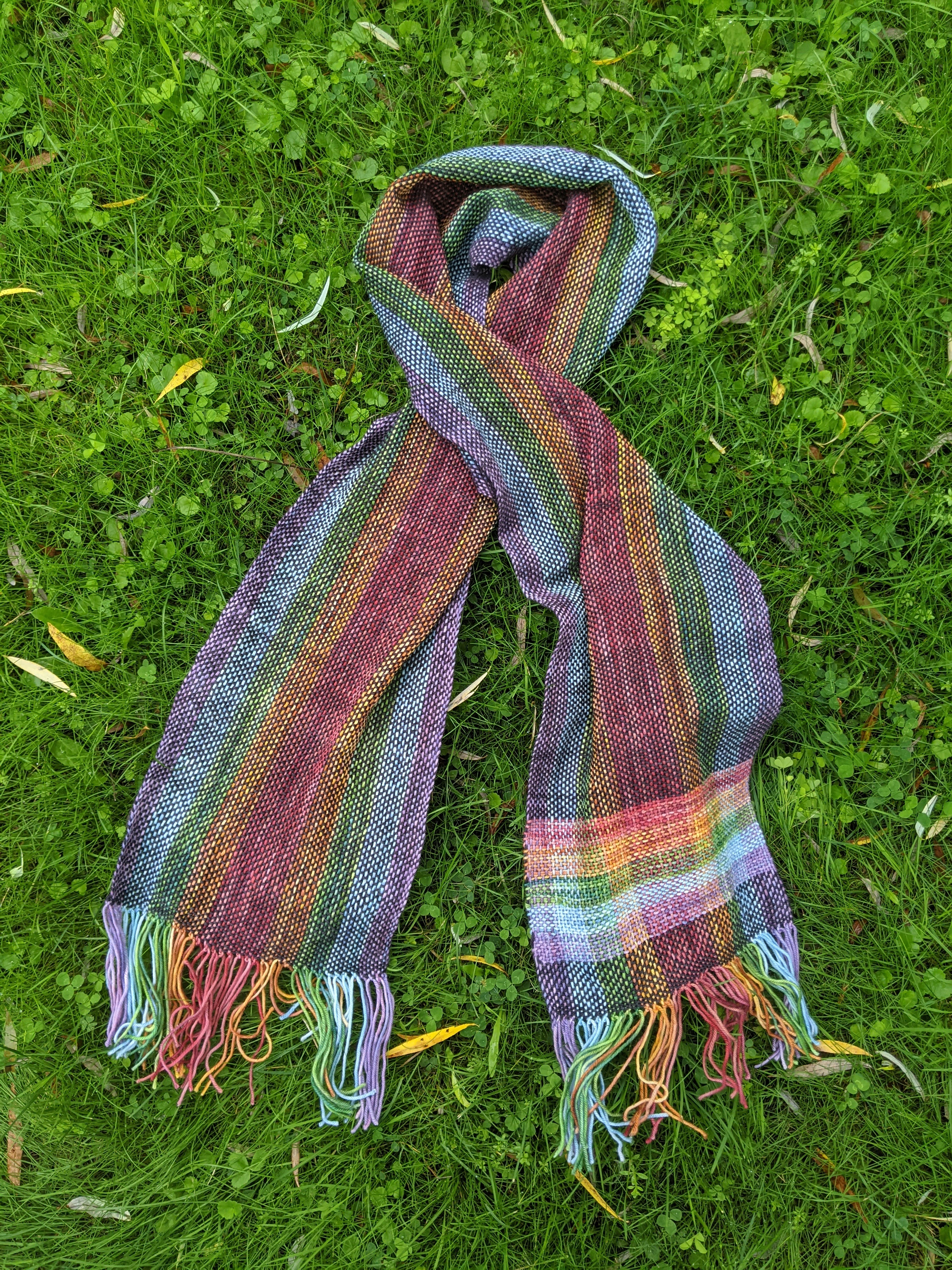A rainbow woven scarf laying gently crossed on green grass.