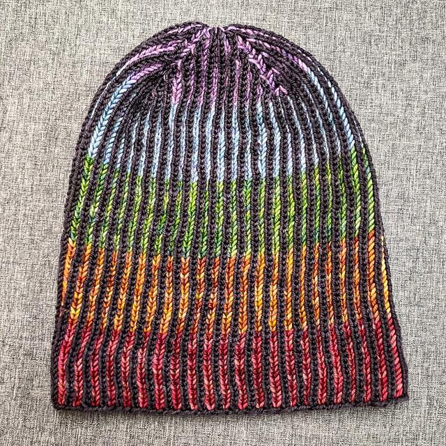 A hat knit in brioche stitch with black stitches set against a rainbow striped background