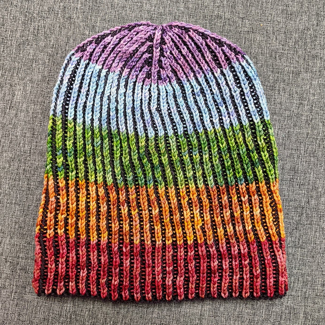 A hat knit in brioche stitch with rainbow stripes against a black background