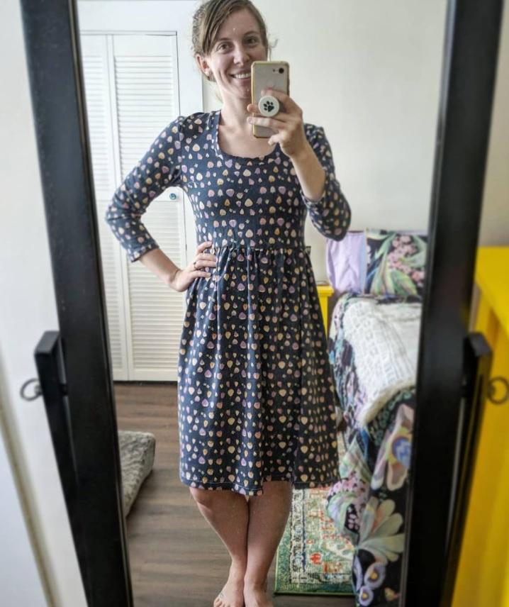 A young woman taking a photo of herself in a floor length mirror wearing a blue handmade three quarter sleeve dress with a strawberry print.