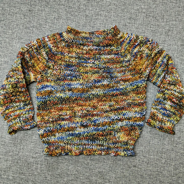 A handknit multicolored baby sweater with a waffle texture.