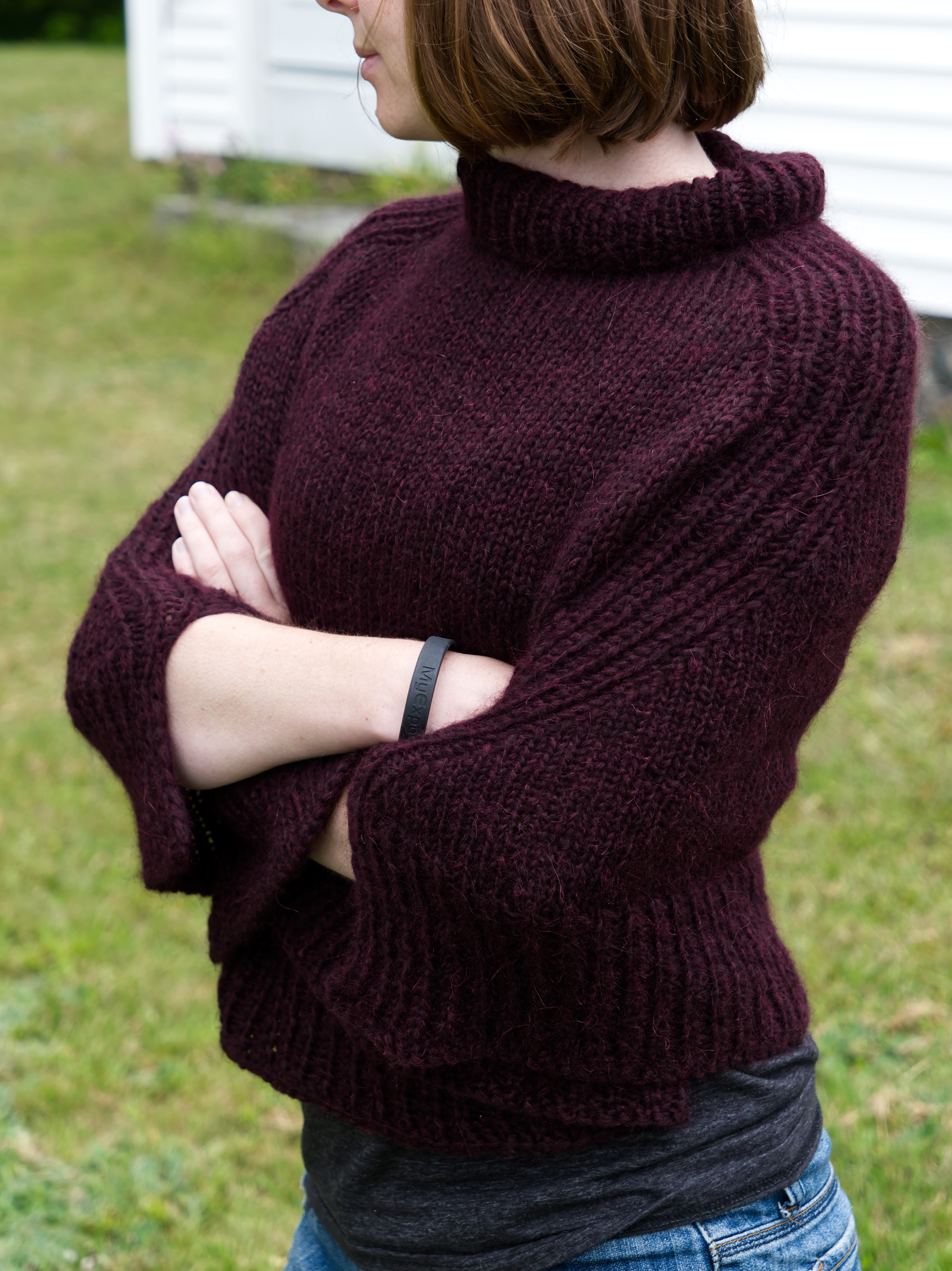 A young woman standing with her arms crossed wearing a plum handknit poncho.