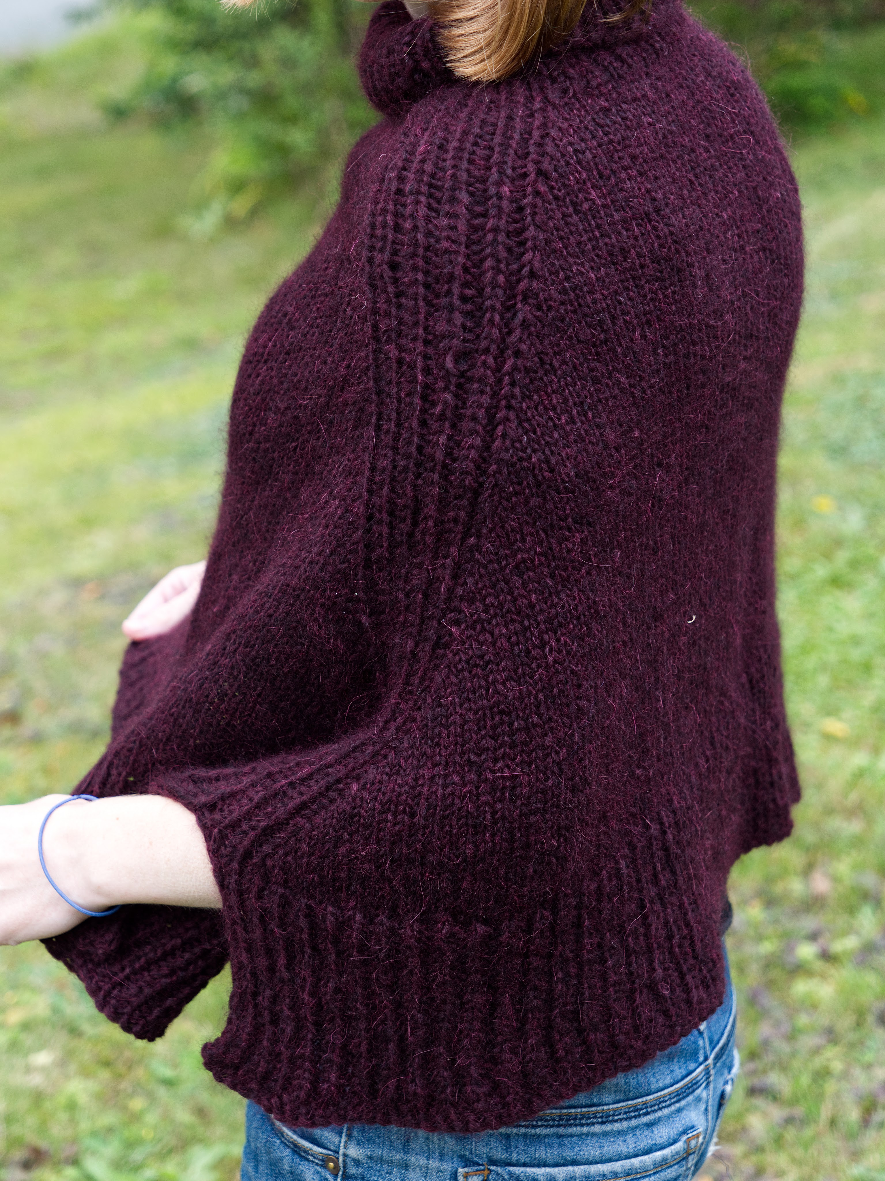A young woman standing sideways to the camera holding the bottom edge of her plum poncho away from her body.
